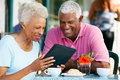 Senior Couple Using Tablet  At Outdoor Cafe Stock Images