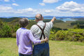 Senior couple on vacation looking at beautiful ocean views a view of islands and mountains bay of islands new zealand Stock Images