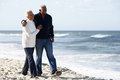 Senior Couple Walking Along Beach Together Royalty Free Stock Photo