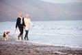 Senior Couple Walking Along Winter Beach With Pet Dog Royalty Free Stock Photo