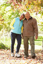 Senior couple walking through autumn woodland smiling Royalty Free Stock Image