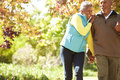 Senior couple walking through autumn woodland smiling Stock Photography