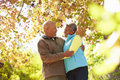 Senior couple walking through autumn woodland smiling at each other Stock Photography