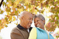 Senior couple walking through autumn woodland smiling at each other Stock Images