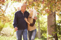 Senior couple walking through autumn woodland smiling at each other Royalty Free Stock Photos