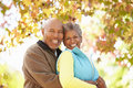Senior couple walking through autumn woodland smiling to camera Stock Images