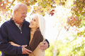 Senior couple walking through autumn woodland smiling to each other Stock Photos