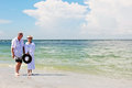 Senior couple walking on beach an elderly hand in hand at the Royalty Free Stock Photography