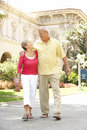 Senior Couple Walking Through City Street Stock Image