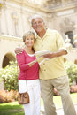 Senior Couple Walking Through City Street With Map Royalty Free Stock Image