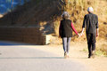 Senior couple walking hand in hand holding Stock Photography