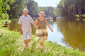 Senior couple walking near lake. Royalty Free Stock Photo