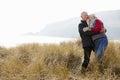 Senior Couple Walking Through Sand Dunes On Winter Beach Royalty Free Stock Photo