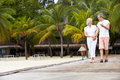 Senior couple walking on wooden jetty toward camera Royalty Free Stock Image