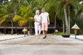 Senior couple walking on wooden jetty toward camera Stock Photo