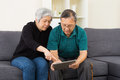Senior couple watching on tablet at home Stock Photography