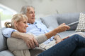 Senior couple watching tv at home sitting in sofa and Stock Image