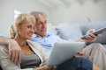 Senior couple watching tv sitting in sofa and Stock Photos