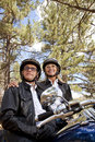 Senior couple wearing helmets stand next to motorcycle Royalty Free Stock Images