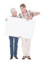 Senior couple with white board lovely holding together a blank over background Royalty Free Stock Photo