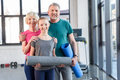 Senior couple with yoga mats and smiling girl standing together in fitness class
