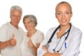Senior couple and young doctor with thumbs up at hospital on white background Stock Photography