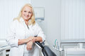 Senior denist in her dental practice smiling standing at chair Royalty Free Stock Photography
