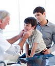 Senior doctor examining little boy's throat Royalty Free Stock Images