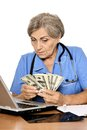 Senior doctor with laptop and dollars