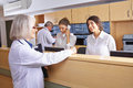 Senior doctor talking with receptionist at hospital reception Royalty Free Stock Photography