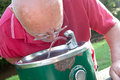 Senior drinking from fountain man water a outside on a sunny day Royalty Free Stock Photos