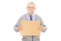 Senior with duct taped mouth holding a blank sign isolated on white background Royalty Free Stock Image