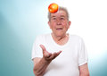 Senior eat healthily throwes an apple in the air Royalty Free Stock Images
