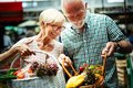 Senior family couple choosing bio food fruit and vegetable on the market during weekly shopping Royalty Free Stock Photo