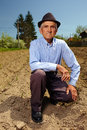 Senior farmer outdoor old on his land on the plowed ground Stock Image