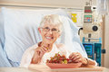 Senior Female Patient Eating Grapes In Hospital Bed Royalty Free Stock Photography