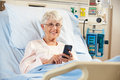 Senior Female Patient In Hospital Bed Using Mobile Phone Royalty Free Stock Photography