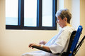 Senior female patient sitting alone in wheelchair looking sad Royalty Free Stock Images