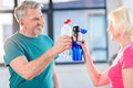 Senior fitness couple holding bottles with water gym