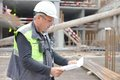 Senior foreman at construction site is inspecting ongoing production according to design drawing Royalty Free Stock Photo