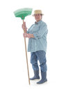 Senior gardener with rake woman wearing straw hat and rubber boots posing over white background Stock Photography