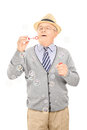 Senior gentleman blowing bubbles isolated on white background Stock Images