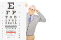 Senior gentleman with glasses standing behind eyesight test isolated on white background Stock Photography