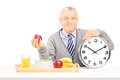 Senior gentleman holding a clock and red apple on table with tray full of drink food isolated on white background Stock Images