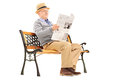 Senior gentleman reading newspaper and sitting on a bench wooden isolated white background Royalty Free Stock Images