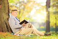 Senior gentleman sitting on a grass and reading a novel in park sunny day Royalty Free Stock Photo