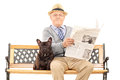Senior gentleman sitting with his dog and reading newspaper Royalty Free Stock Photo