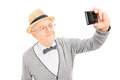 Senior gentleman taking a selfie with cell phone isolated on white background Royalty Free Stock Photography