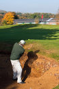 Senior golfer playing out of a bunker in autumn Stock Photo