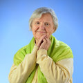 Senior happy woman with grey hairs against blue background Royalty Free Stock Image